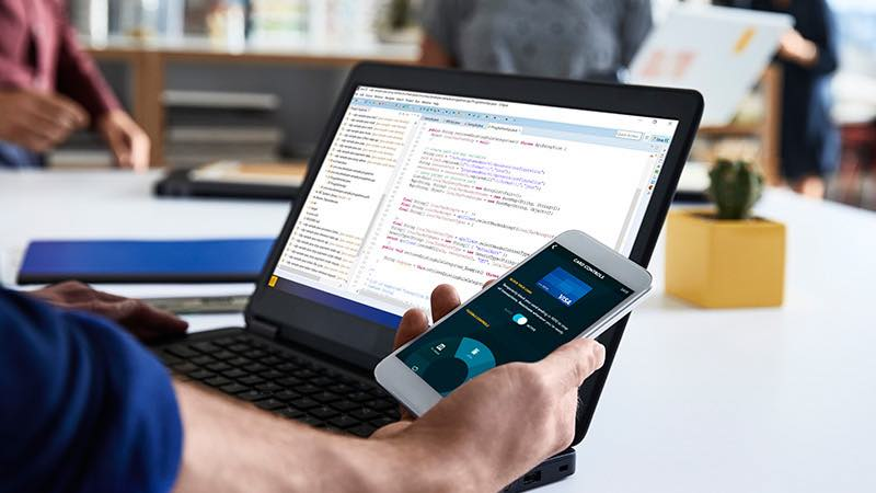 Developer in office environment with open laptop looking at smart phone.