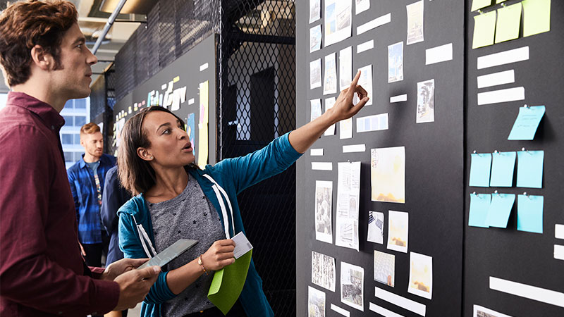 Man and woman discussing an item on a Scrum Task Board.